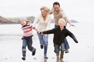 Family running on beach holding hands smiling